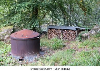 Charcoal burner & log store in a woodland setting