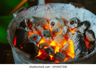 Charcoal burning inside an iron bucket