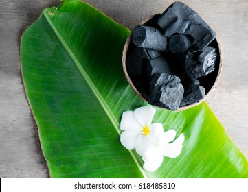 charcoal in coconut shell for spa on the wood background with flower on banana leaf for advertisement