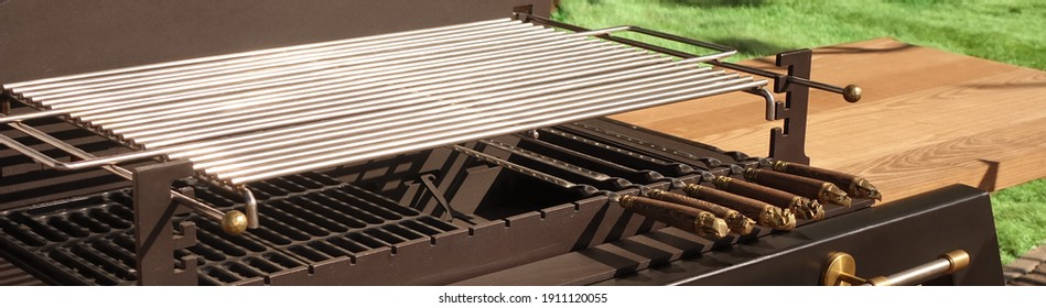 Charcoal Empty And Clean BBQ Grill . Outdoor Backyard Kitchen Table With BBQ Charcoal Grill Appliance. Family Garden Party Barbecue Grill, Closeup View, Green Backyard Lawn In The Background.