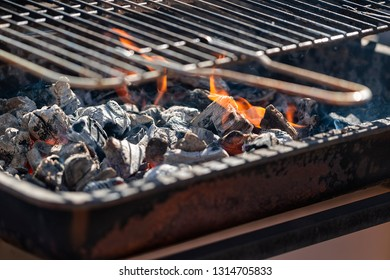 Charcoal with flame and grill.