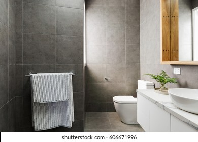 Charcoal grey modern bathroom with marble benchtop and wood mirror