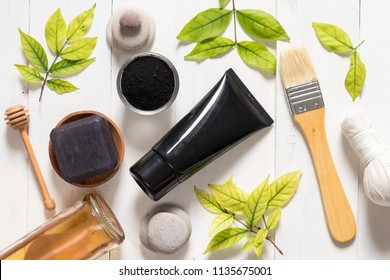 Charcoal mask tube on white background, cosmetic and skincare products, flat lay objects