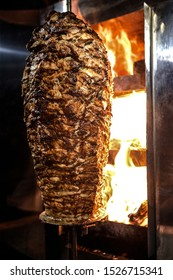 Charcoal shawarma meat. Closeup of chicken meat collected on a vertical skewer and grilled on charcoal.