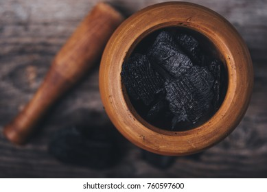 Charcoal in a wooden mortar on board