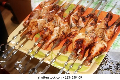 Charcoal-fried chicken legs strung on a skewer on a tray