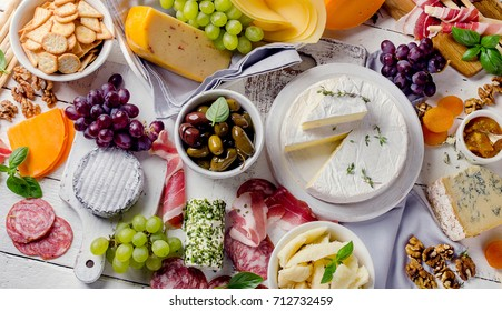 Charcuterie assortment, cheeses, olives and fruits   on a white wooden background.