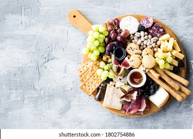 Charcuterie board. Cheese platter: Parmesan, maasdam, camembert, cheddar, gouda with prosciutto, salami, fruits and nuts. Assortment of tasty appetizers or antipasti. Top view. Copy space.