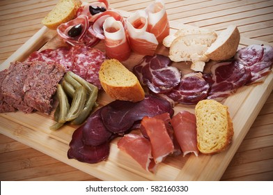 Charcuterie board with cured meat, bread and olives