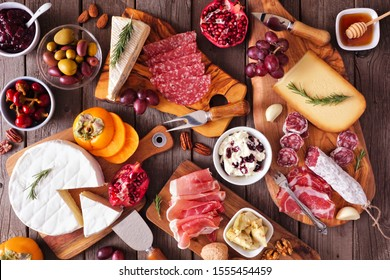 Charcuterie boards of assorted cheeses, meats and appetizers. Above view table scene on a rustic wood background.