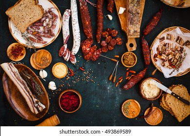 Charcuterie concept. Overhead view of cured meats, sausage with mustard sauce on rustic dark table.
