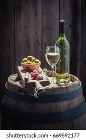 Chardonnay wine, olives and cold cuts on oak barrel