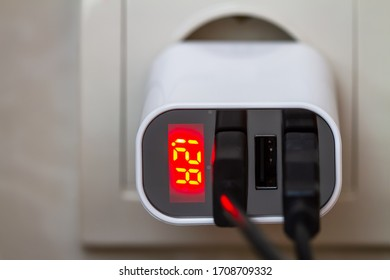 The charger is plugged in. Mobile devices are charging from socket charger for three USB ports output with amperage indicator. Closeup, selective focus