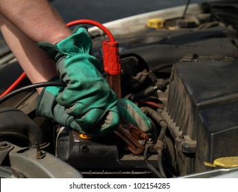 Charging battery in car by mechanic in gloves