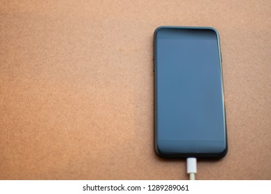 Charging battery mobile phone with blank screen on the wooden table. Selective focus.