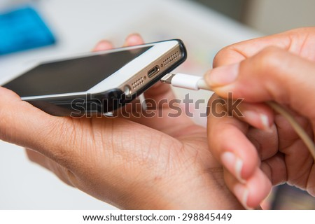 charging battery on mobile phone, hand