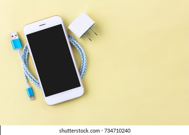 charging cables with smartphone and tablet on yellow background in top view