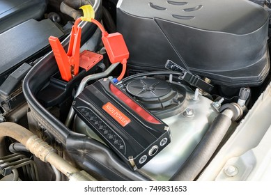 Charging car battery / battery maintenance concept : Red and black automotive clip connects to a positive and negative pole slot to deliver electric current or transfer energy to start motor / engine.