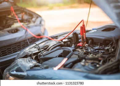 charging car with electricity through cables, start a car's.safely jump start a dead battery concept.