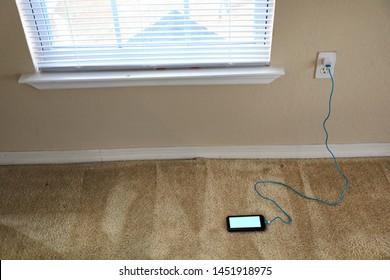 charging cellphone pluged in wall outlet in domestic house empty living room