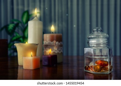 Charging distilled water with crystal energy by carnelian tumbled stones in a glass jar. There are four lit candles on the wooden table.