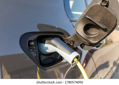 charging electric car at home in the sun