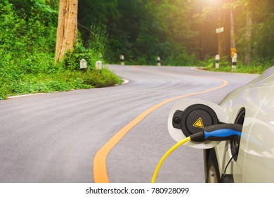 Charging an electric car with the power cable supply plugged in country road,copy space.