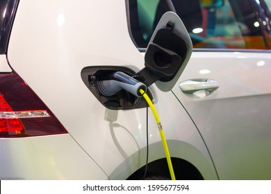 Charging an electric or hybrid PHEV car with the power cable supply plugged in. Electric car charging station