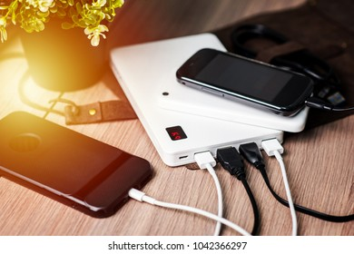 Charging the empty battery smartphone with white power bank. Shallow depth of field.