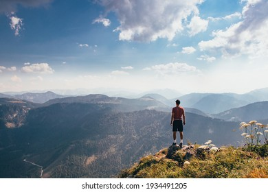 Charging energy in wild Austrian nature. Athlete of lighter figure with cap and red elastic trick stands on the edge of rock and enjoys feeling of relaxation and freedom. Conquering Mount Otscher.