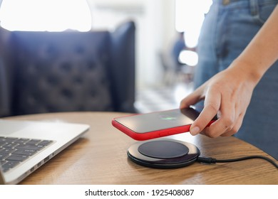 Charging mobile phone battery with wireless charging device in the table. Smartphone charging on a charging pad. Mobile phone near wireless charger