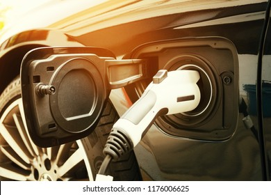 Charging modern electric car battery on the street which are the future of the Automobile, Close up of power supply plugged into an electric car being charged for hybrid . New era of vehicle fuel.