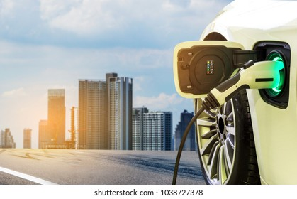 Charging modern electric car on the street with blurred building city on background.  Eco-friendly alternative energy concept.