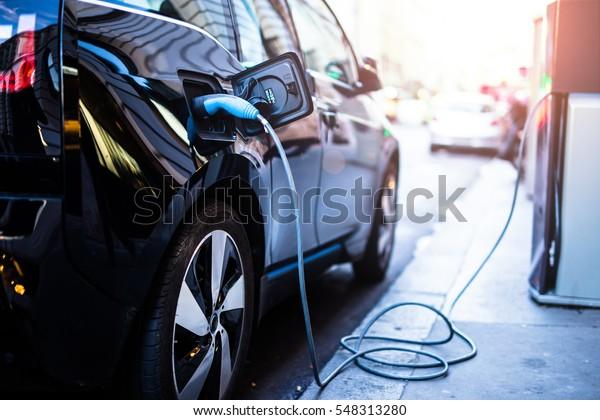 Das Aufladen von modernen Elektroautos auf der Straße, die die Zukunft des Automobils darstellen