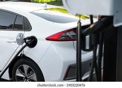 Charging modern electric car from station outdoors