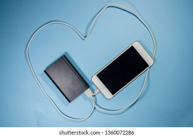 A charging phone with powerbank on blue background. Keep the battery charged on your device anyway you go. Technology connect with white cord cable in the shape of the heart concept.