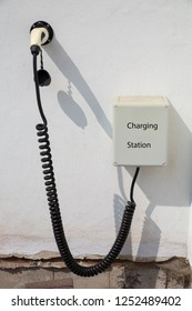 Charging point for electric car on white wall of house