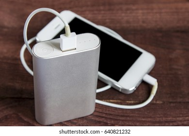 Charging Smartphone With Grey Portable External Battery ( Powerbank )  On A Wooden Background .