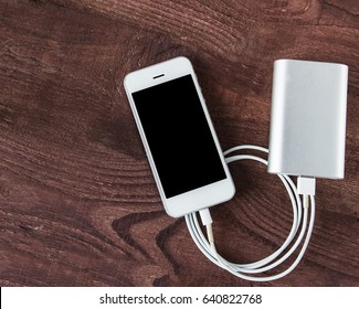 Charging Smartphone With Grey Portable External Battery ( powerbank ) on Wooden Table .