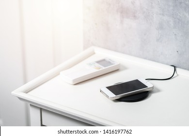 Charging the smartphone with wireless charger on the white desk.