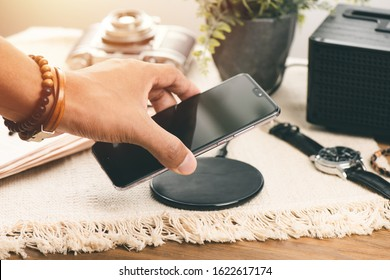 Charging the smartphone with wireless charger on wooden desk. Modern lifestyle concept.