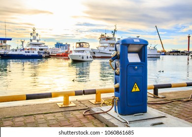 Charging station for boats, electrical outlets to charge ships in harbor. Shore in marina jetty. Electrical power sockets bollard point on pier near sea coast. Luxury yachts docked in port at sunset.