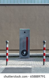 """""""Charging station for electric cars"""" written in German in the streets in the sun"""