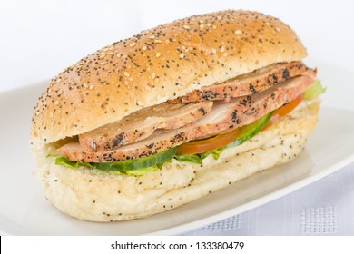 Chargrill Chicken Sandwich - Chargrill chicken breast slices, honey mustard mayonnaise, tomato, cucumber and lettuce in a white bun with sesame seeds.