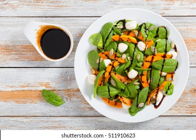 Chargrilled pumpkin, mini mozzarella and spinach salad seasoned with pumpkin seeds on white plate with caramelized balsamic vinegar dressing,  easy and healthy recipe, view from above
