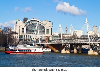 Charing Cross Station and the Jubilee Bridge in London with passenger ships in the river Thames