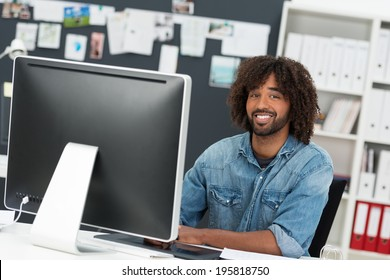 Charismatic African American businessman with an afro hairdo sitting at his desk with a desktop monitor smiling at the camera