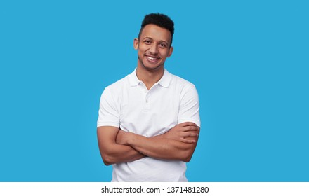 Charismatic African American male in white polo shirt keeping arms crossed and smiling while standing against blue background