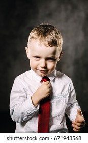 Charismatic boy straightens his tie with a serious face