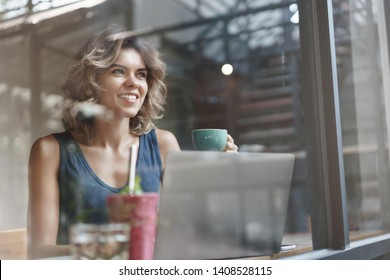 Charismatic charming european blond curly-haired successful woman drink coffee enjoy lunch sit cafe window bar look outside delighted taste coffee hold cup use laptop, researching, working freelance